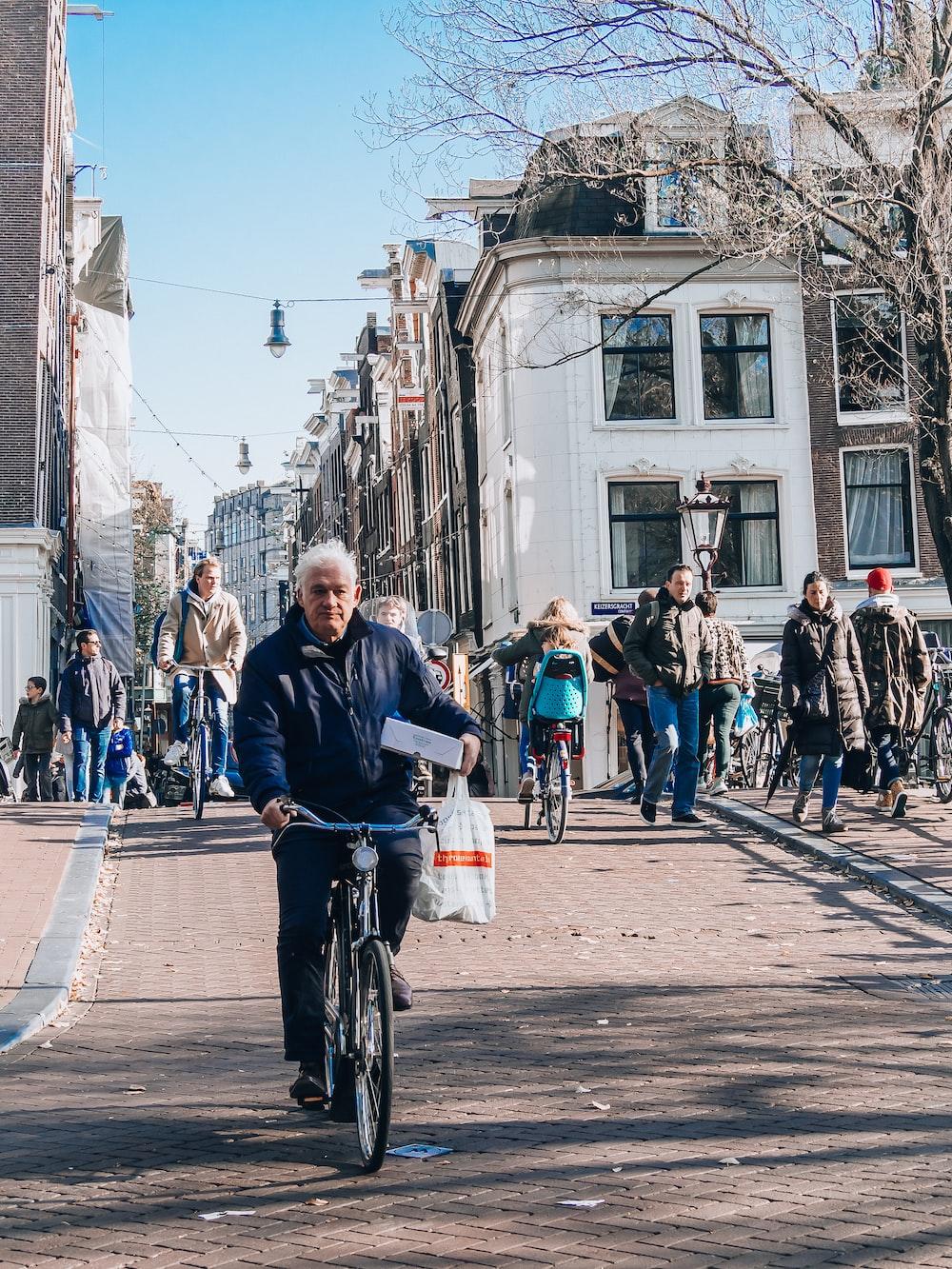 shallow focus photo of man riding bike during daytime