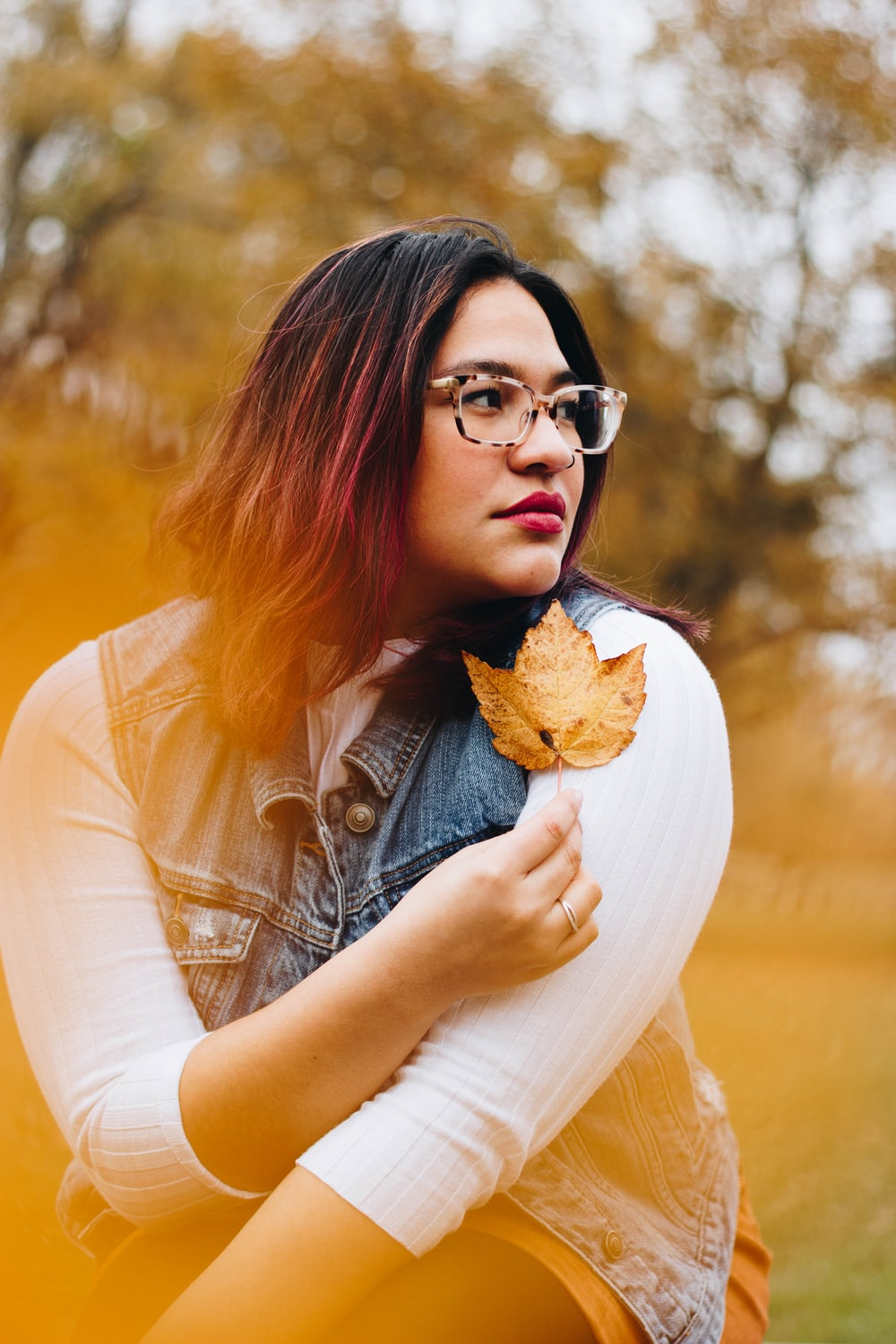 photo shoot of woman holds dried leaf near to her left shoulder