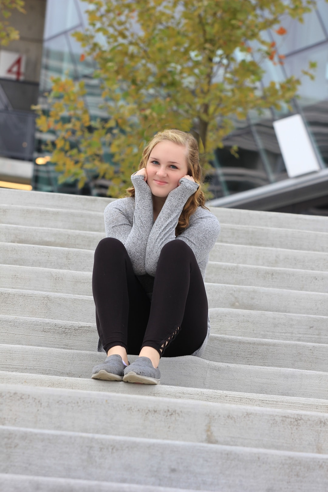 A girl poses on concrete steps in a grey sweater.