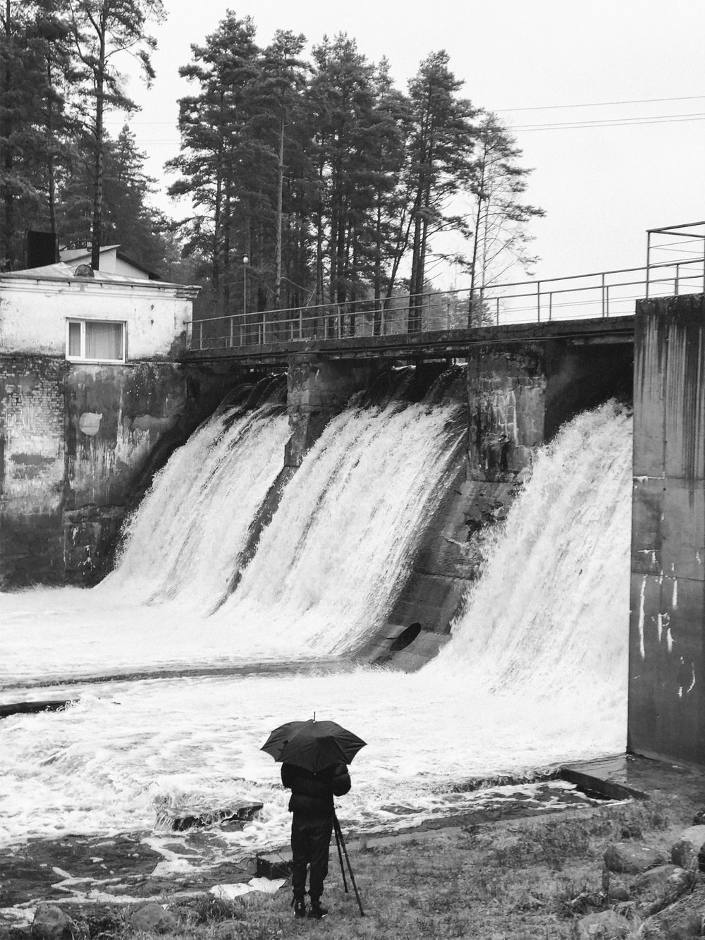 grayscale photo of person under umbrella in front of dam