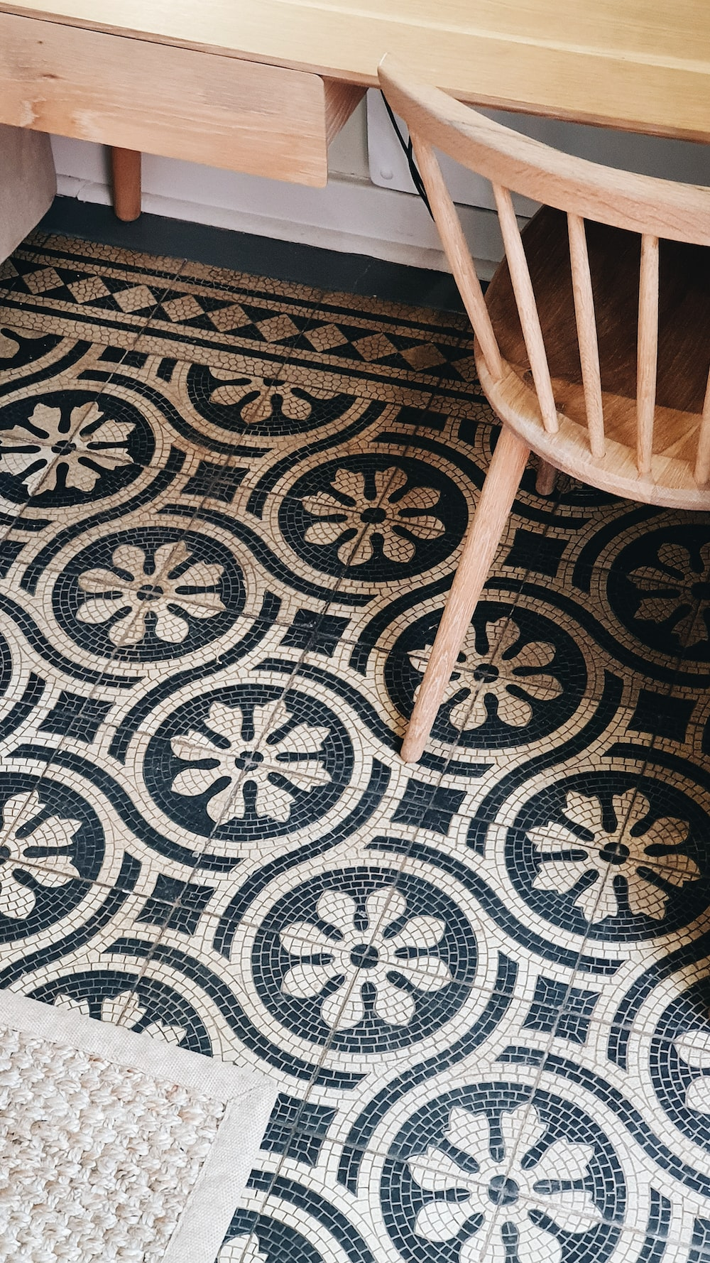 brown wooden chair on gray and black floral area rug
