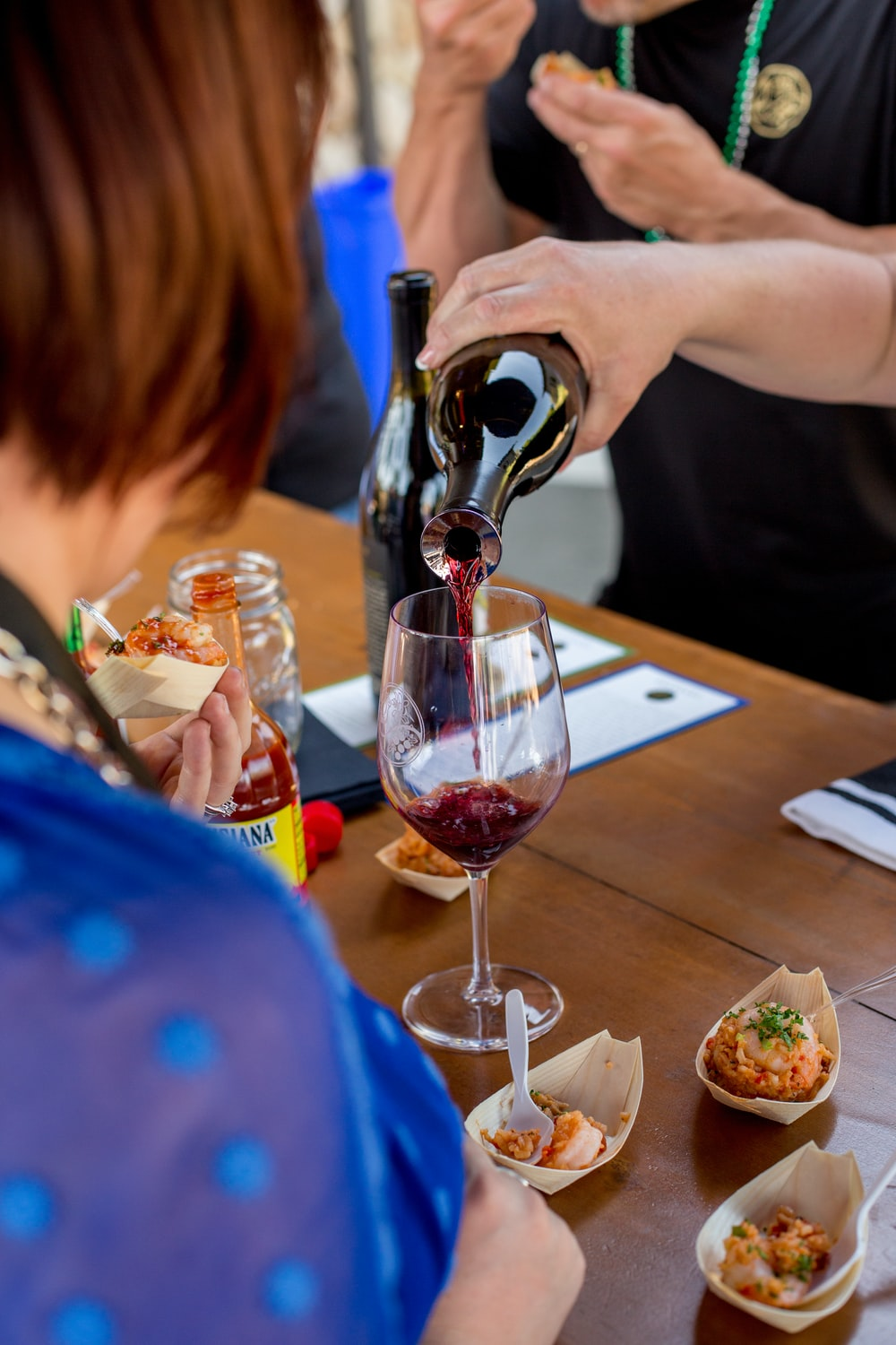 person pouring wine on glass in front of woman in blue top