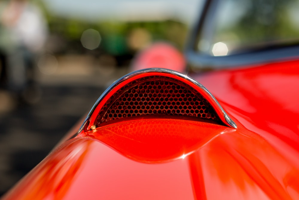 selective focus photography of red vehicle's hood