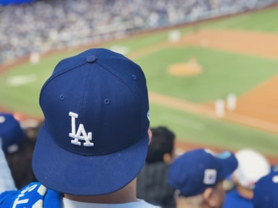 selective focus photography of person wearing la dodgers cap looking at field dodgers teams background