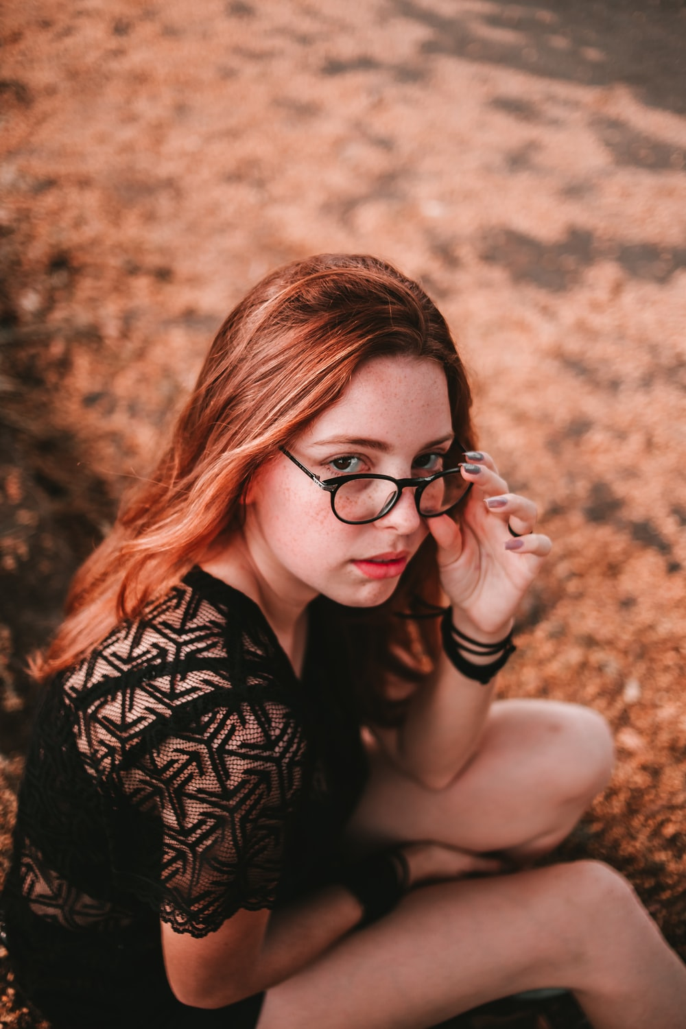 selective focus photography of sitting woman wearing black dress holding her eyeglasses