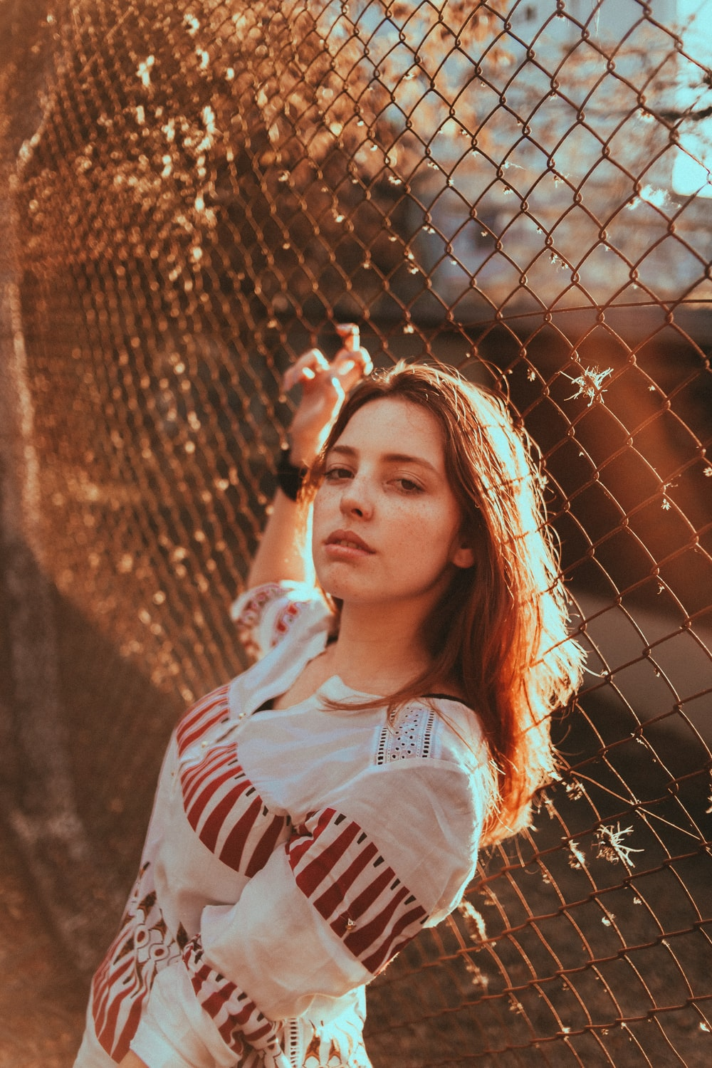 selective focus photography of woman standing beside chain link fence during daytime