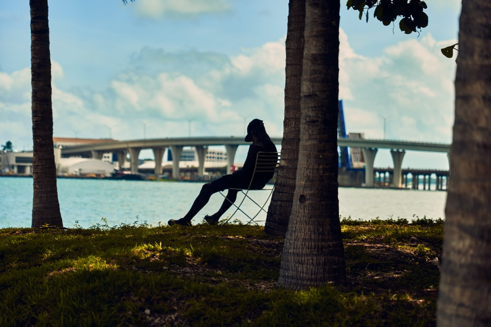 person wearing cap sitting on chair under tree beside body of water during daytime