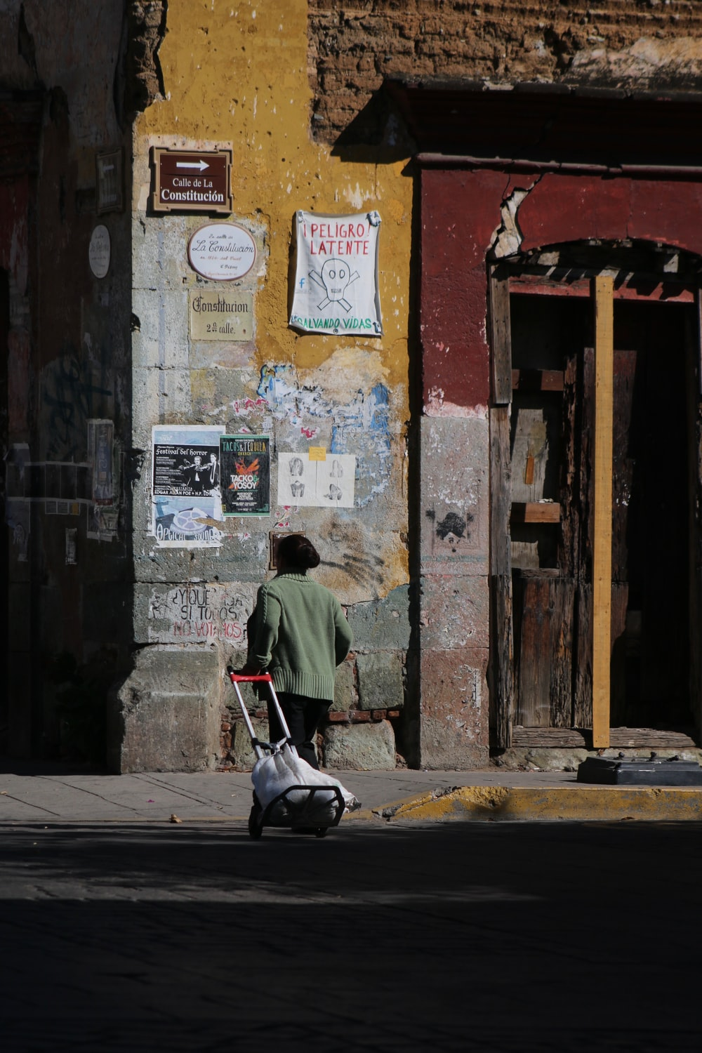photography of girl pulling a trolley toward building during daytime
