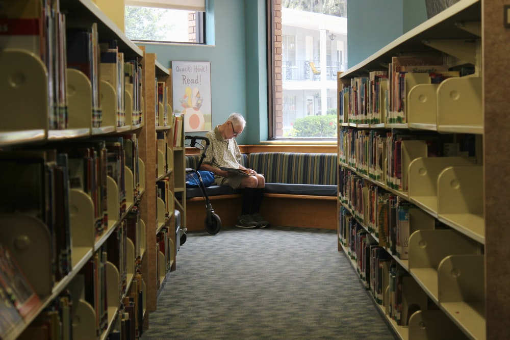 man reads book at the library