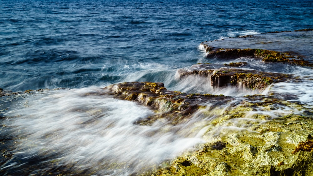 body of water crashing on rocks