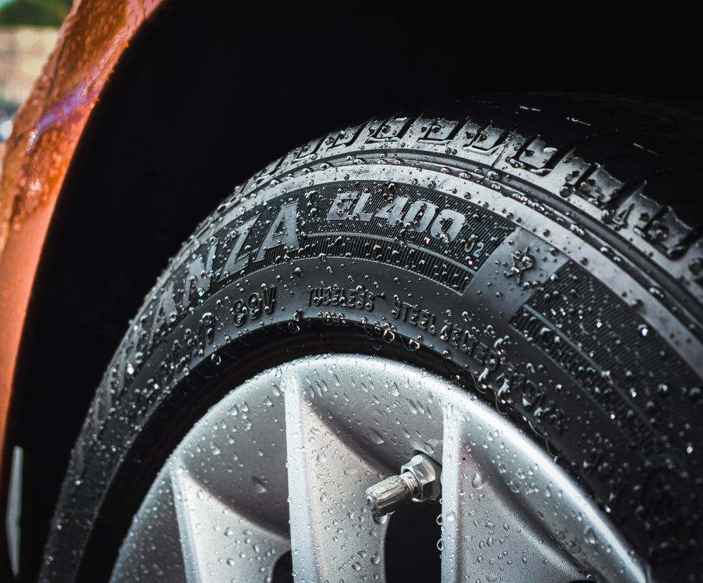 shallow focus photography of silver car wheel and car tire