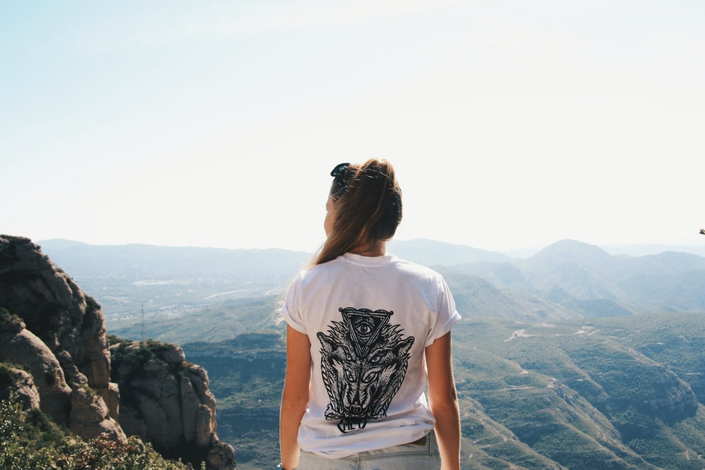 woman in white and black t-shirt standing on cliff looking at mountain during daytime