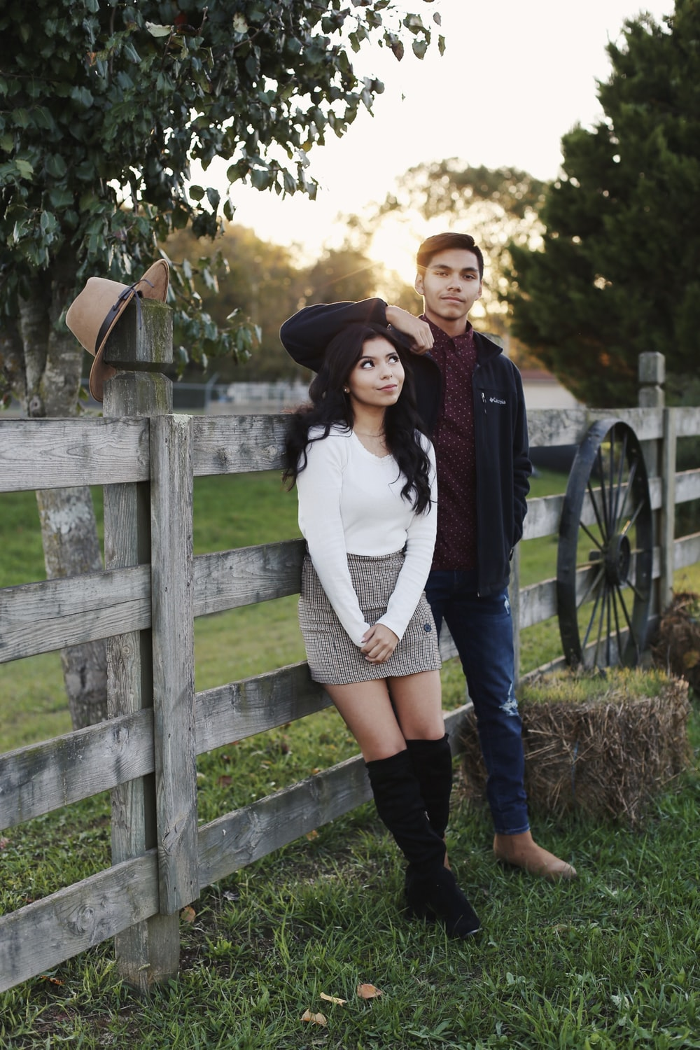 man and woman leaning against a wooden fence