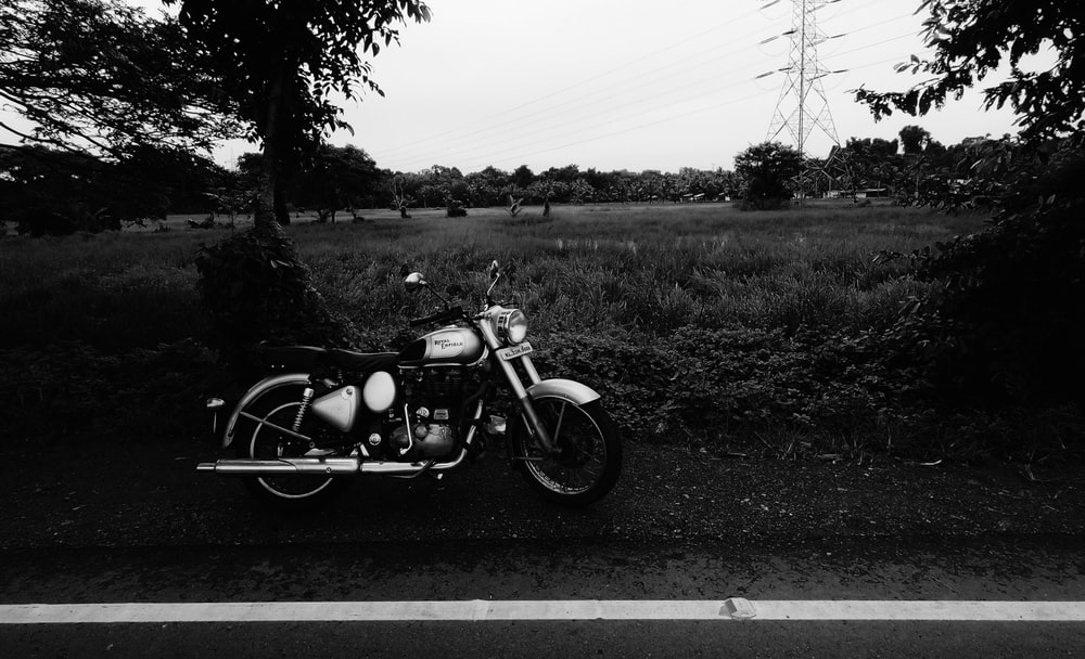 grayscale photography of motorcycle parked beside road