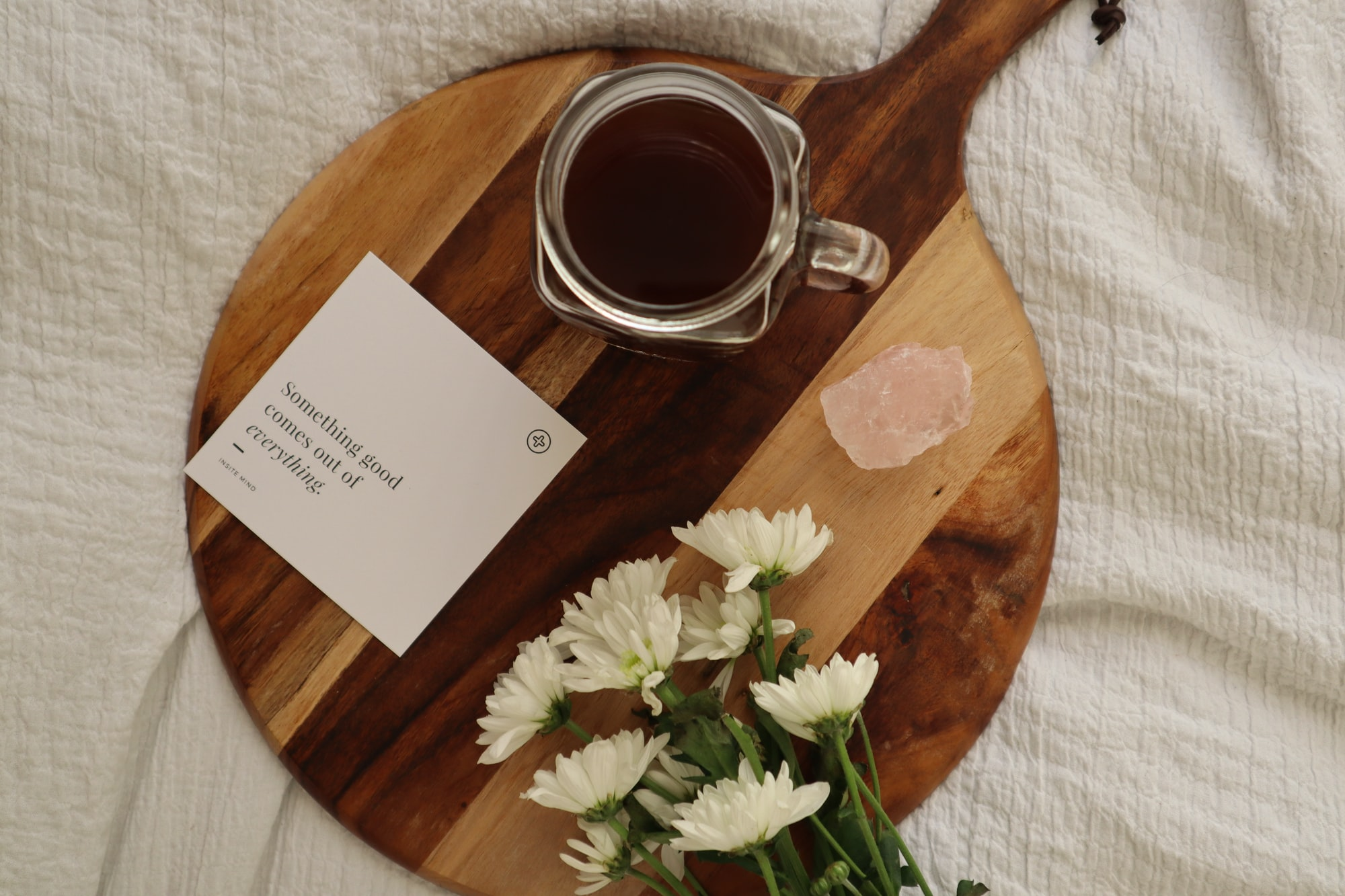 Affirmation card, black coffee, flowers and crystal in bed (card by insite mind)