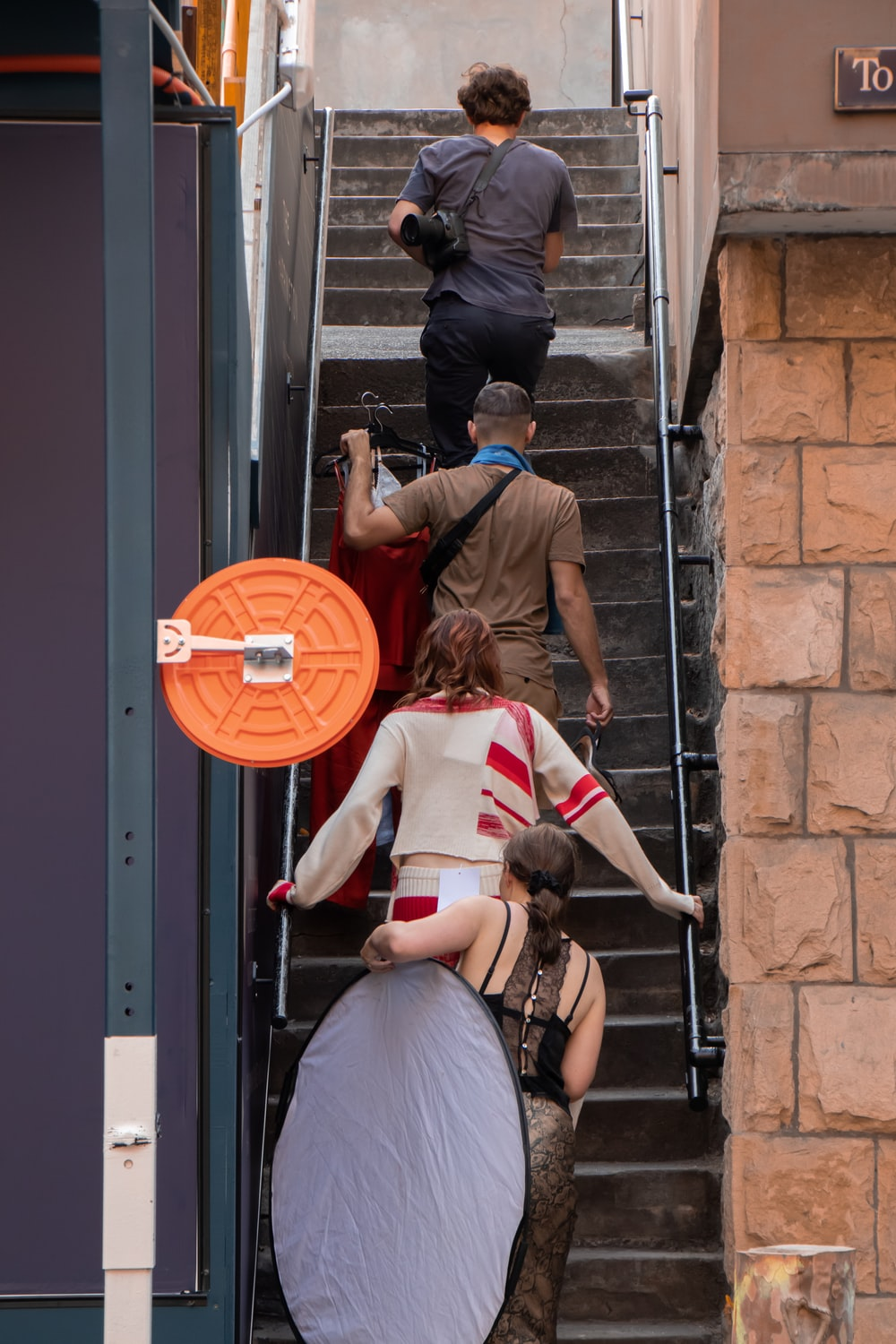 four people walking on stairs