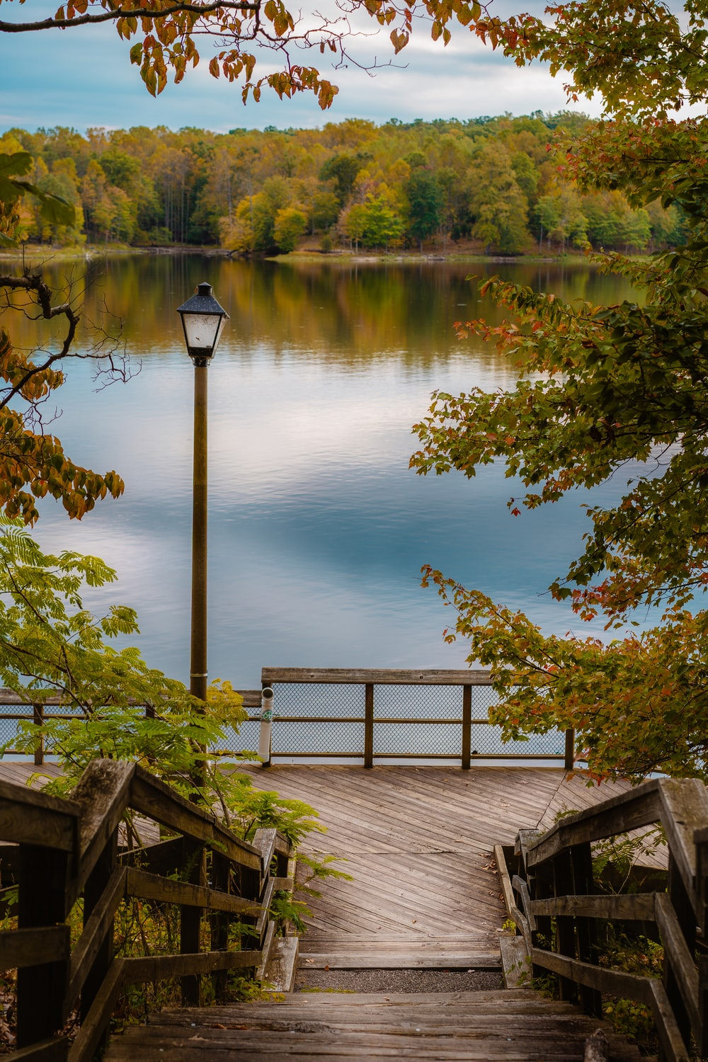 lamp post and wooden deck beside body of water