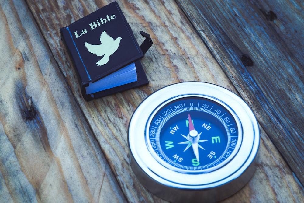 round silver compass beside La Bible