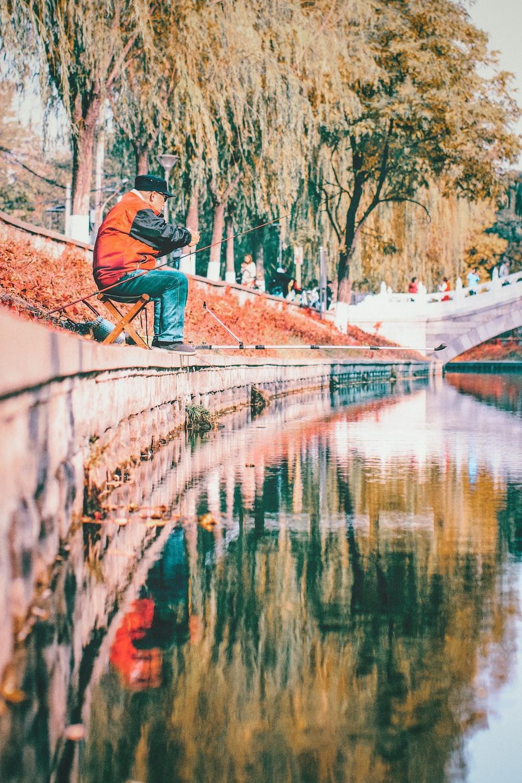 man wearing orange and black jacket fising on lake
