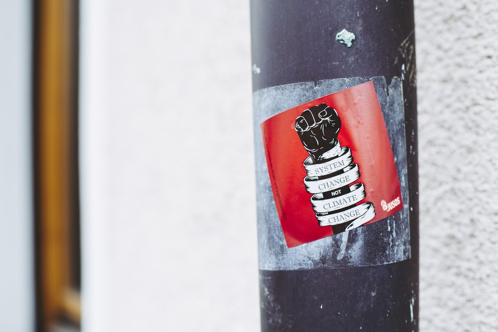 black and white fist-printed poster on a metal post