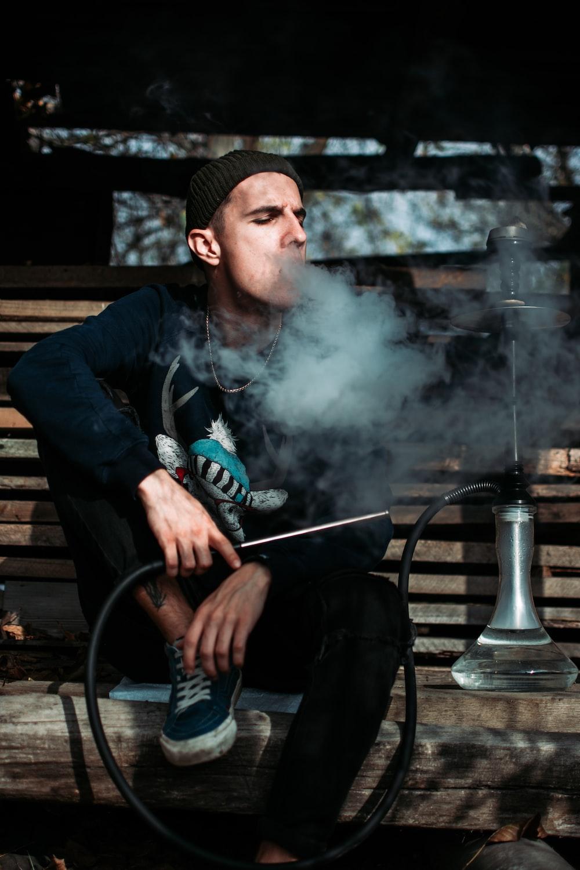 man sitting on brown bench smoking outdoors