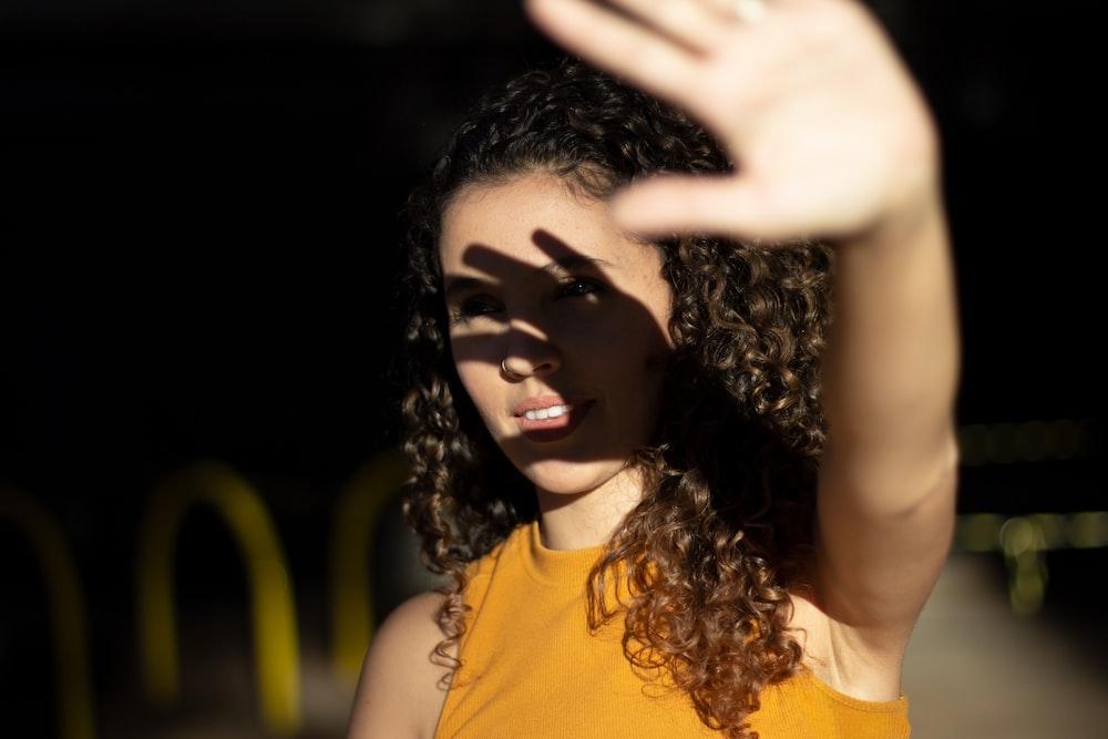 woman raising her left hand
