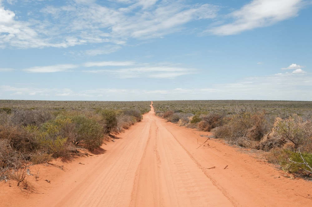 dirt road under blue sky