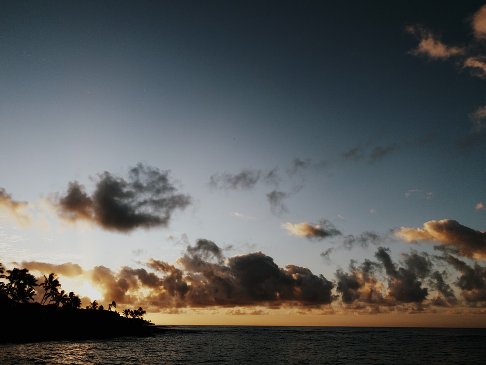 gray clouds and silhouette of island
