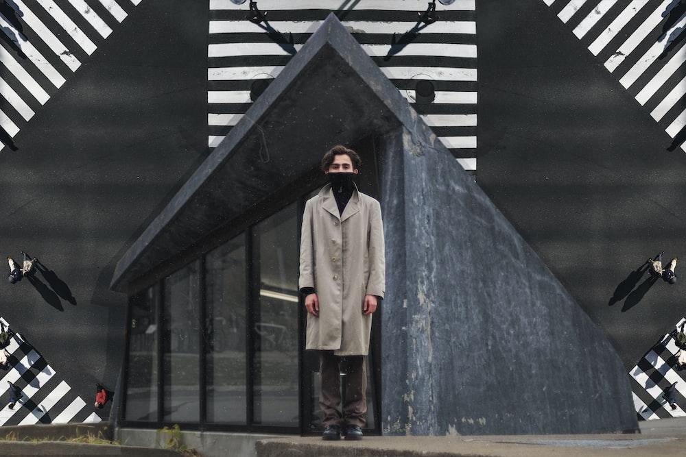 man in gray coat and brown pants standing