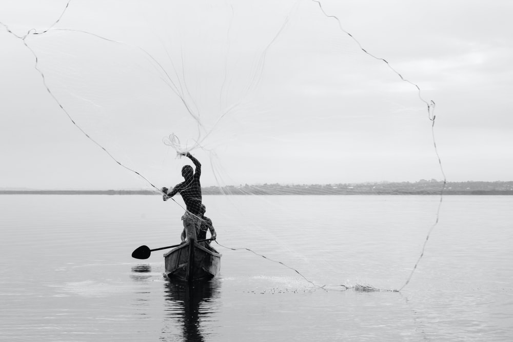 grayscale photography of person in boat throwing fishing net