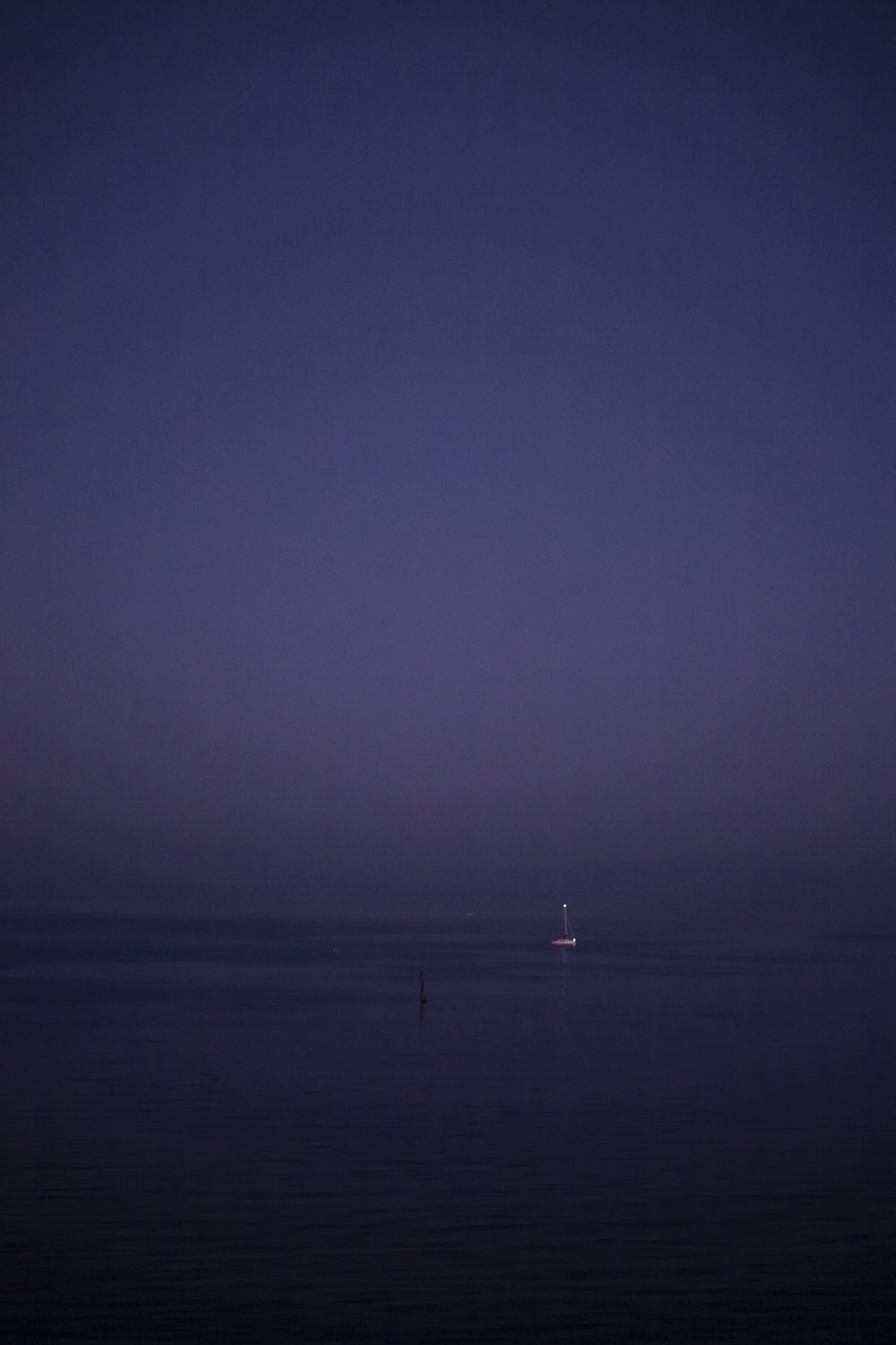 body of water under gray sky at night