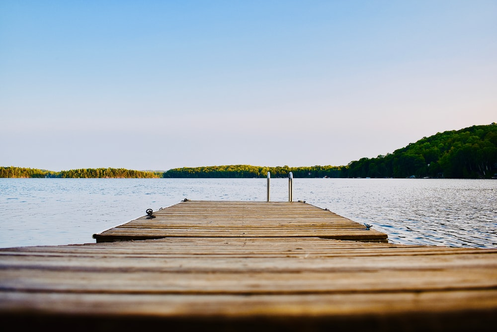 brown wooden dock on calm body ofwater
