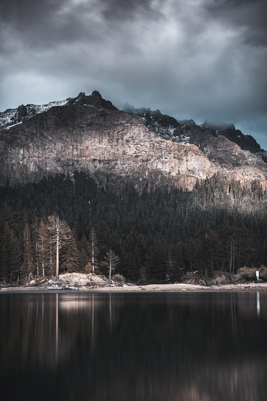 lake by mountain under gray skies at daytime