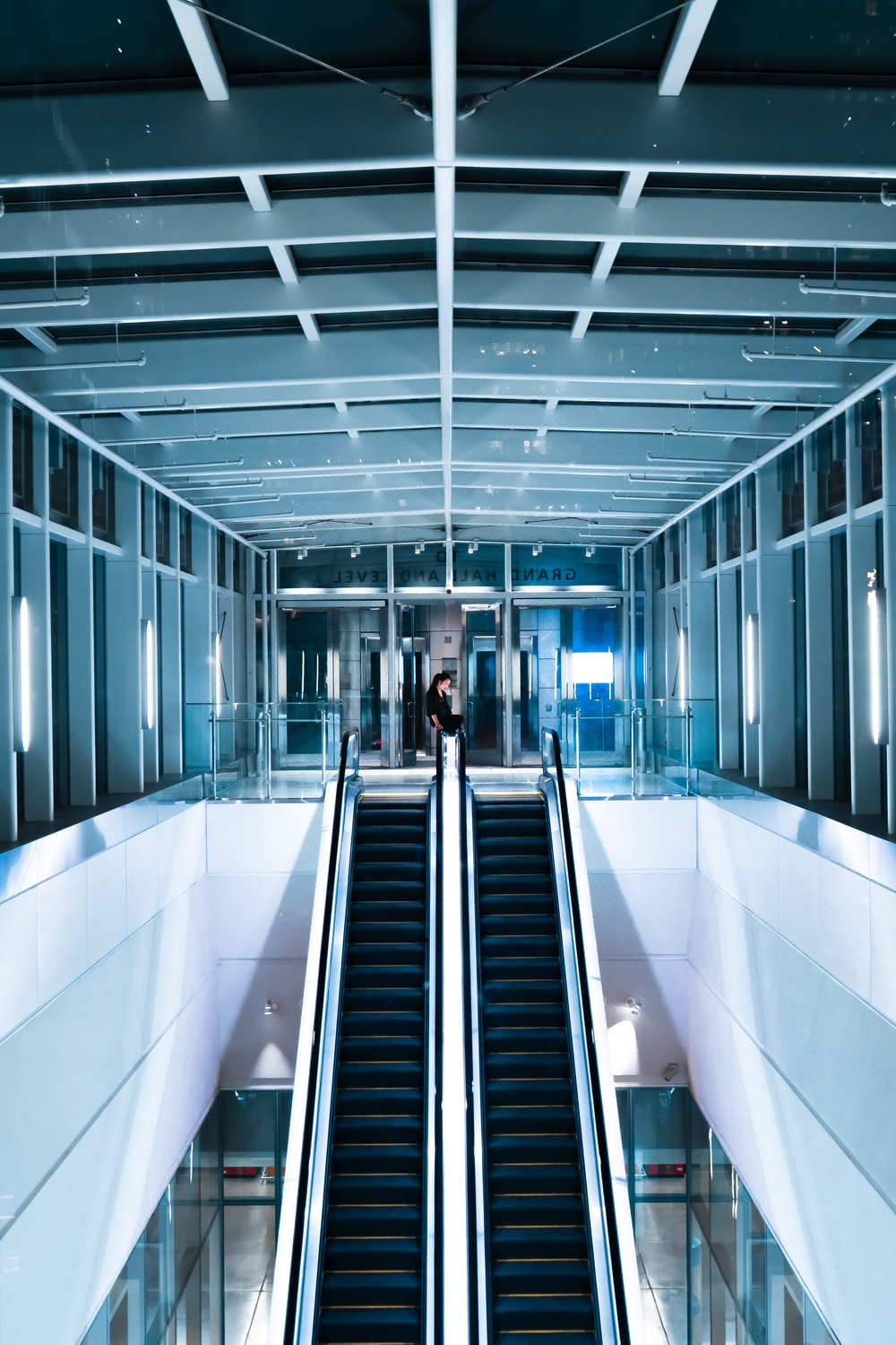 person in black shirt standing beside escalator
