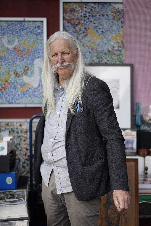 man with white long hair wearing black jacket standing