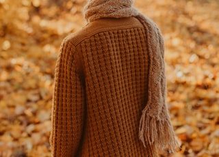 selective focus photography of wearing brown scarf walking beside trees