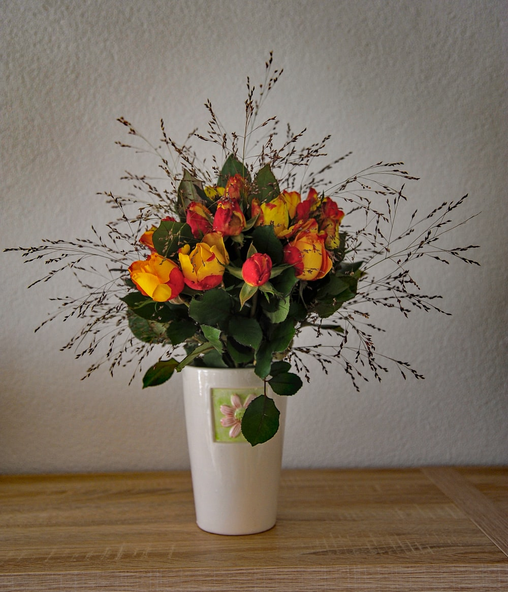pink and yellow flower arrangement in white ceramic vase