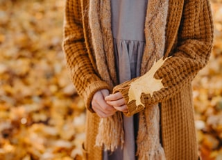 woman wearing brown knitted cardigan and scarf