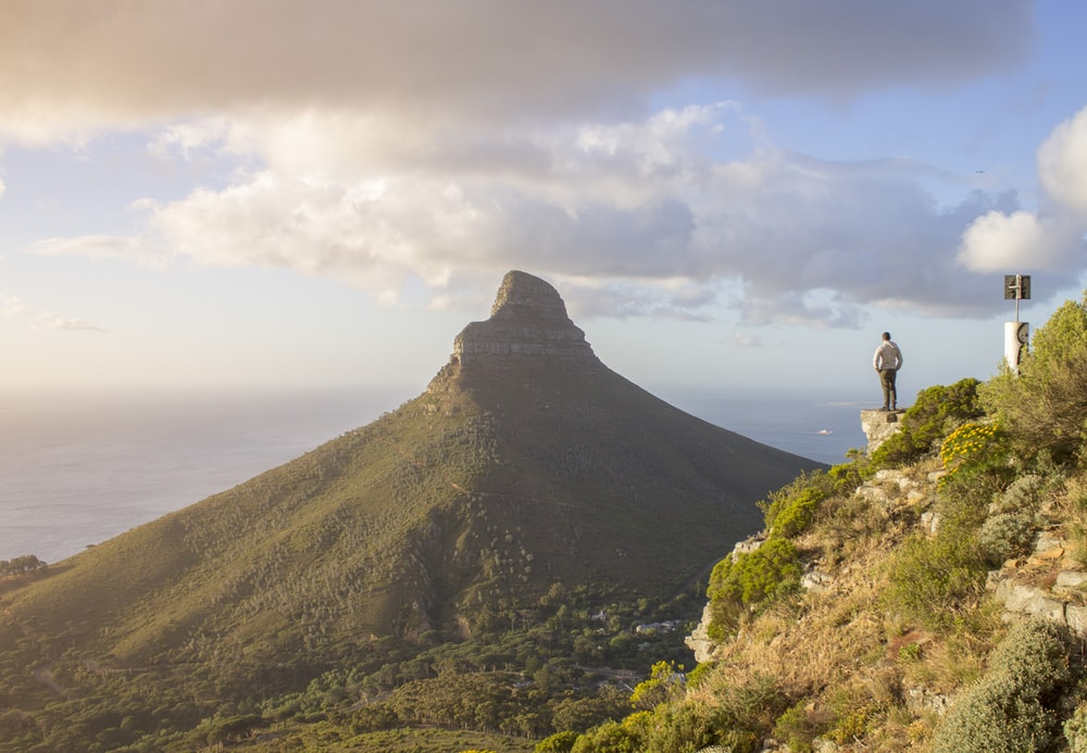 man standing on cliff facing green mountain
