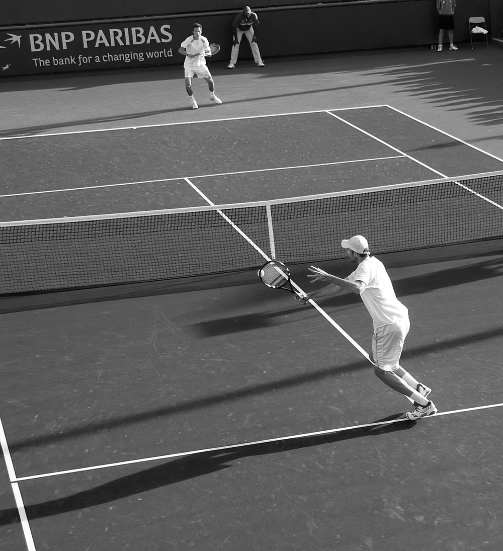 two men playing lawn tennis in grayscale photography