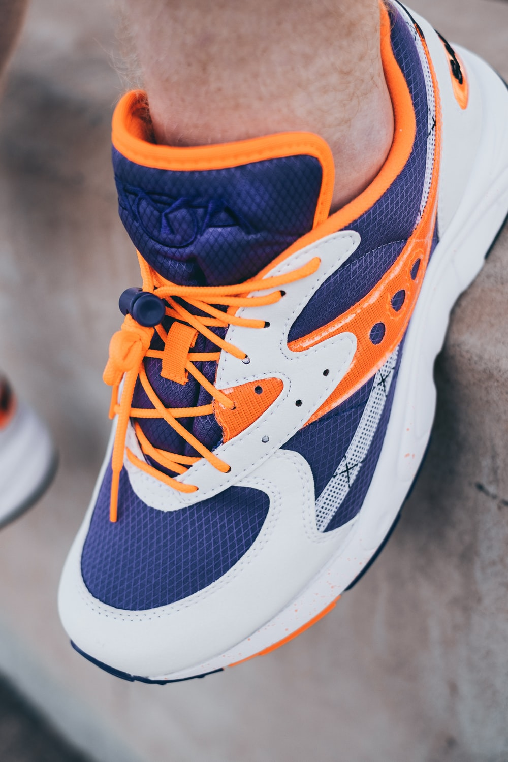 unpaired blue, white, and orange Saucony sneaker