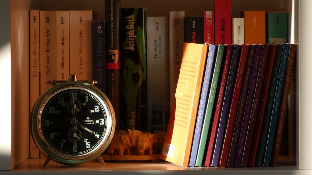 silver alarm clock on shelf full of book