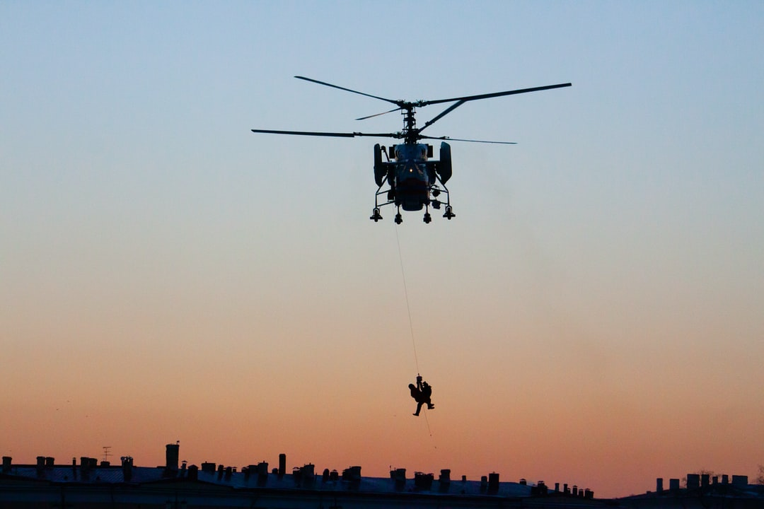 A rescuer hoists a victim into a helicopter.