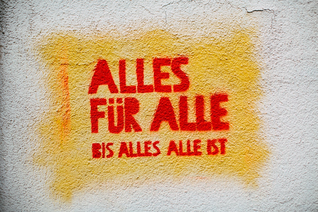 """Urban street art graffiti on the wall: """"Everything for everyone until everything is gone"""" in German: """"Alles für alle bis alles alle ist"""""""