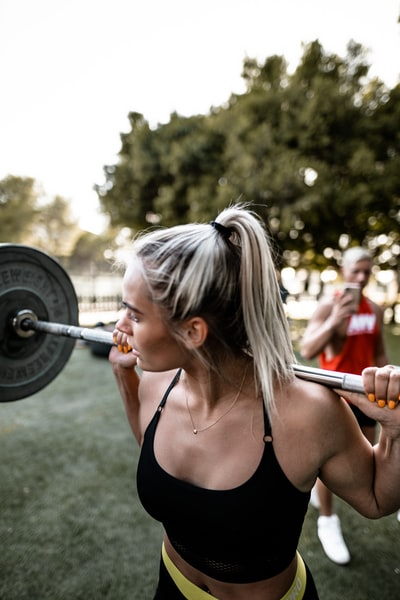 woman in black sports bra carrying barbell