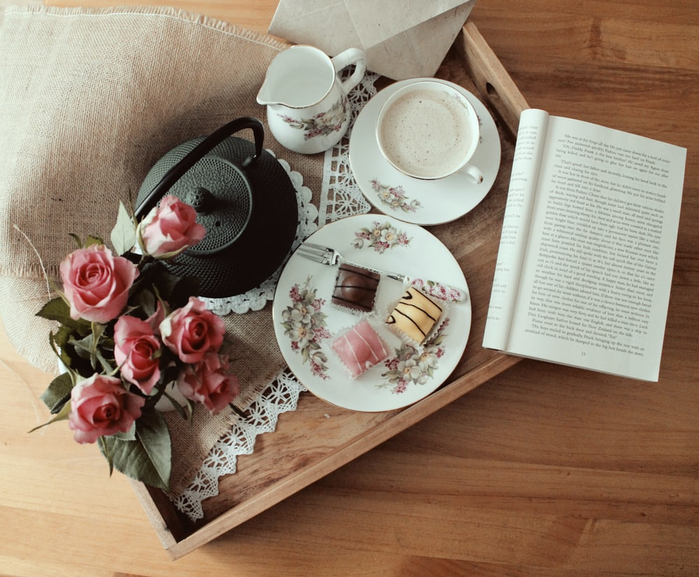 black kettle, plate, teacup, and saucer on brown tray