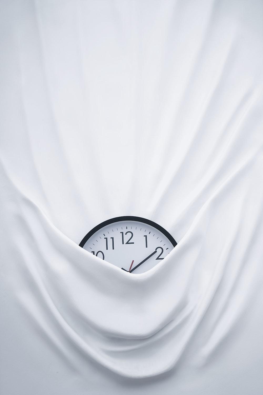 round black clock on linen