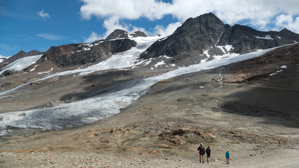 three people standing near mountain with clouds