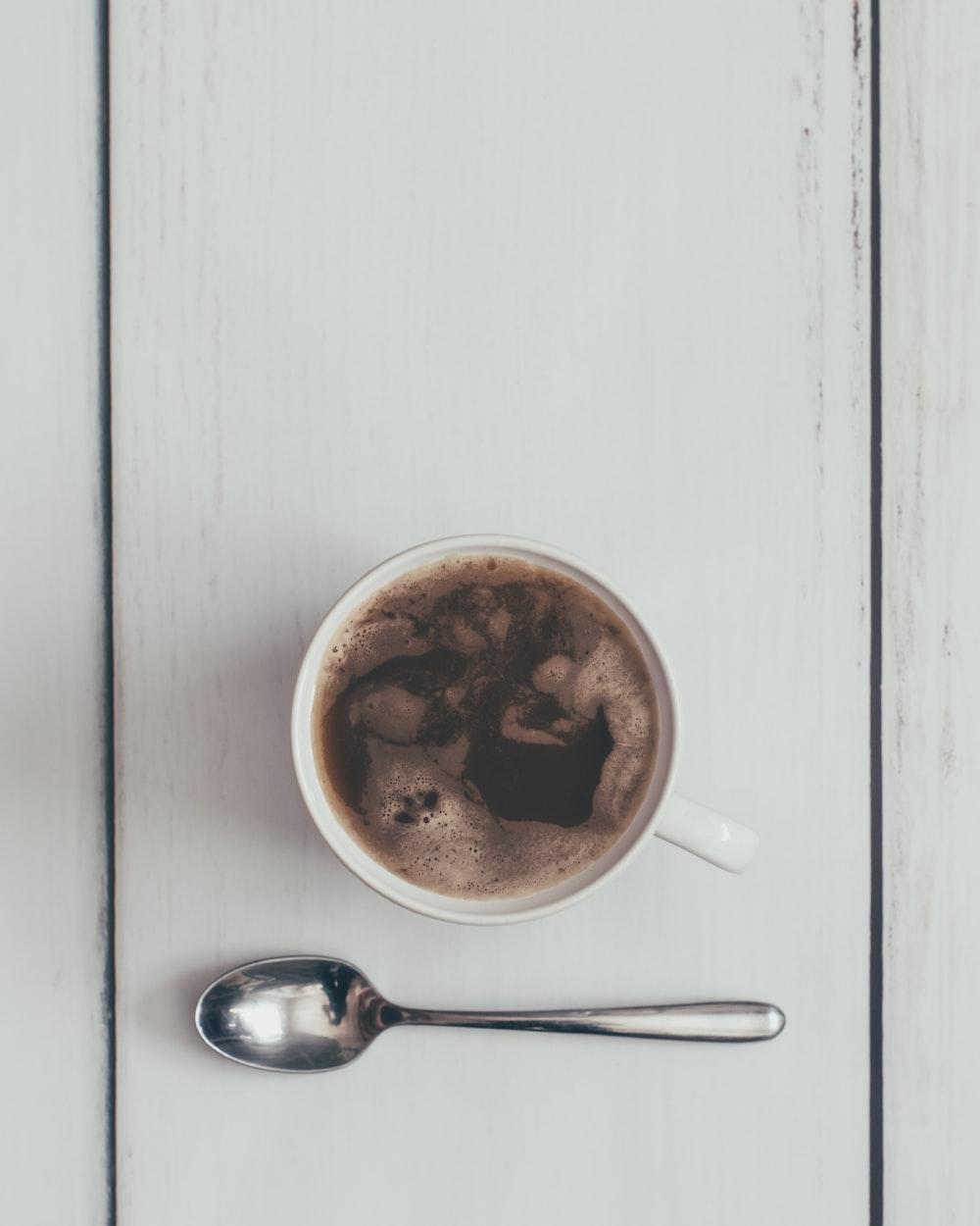 coffee filled teacup by teaspoon