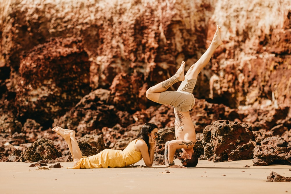 photography of woman lying on sand in front of man during daytime